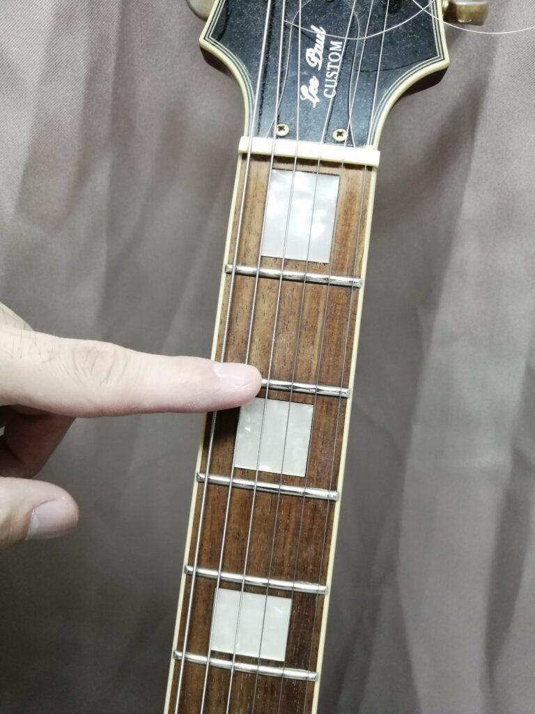 ギターのフレットを指さしている画像