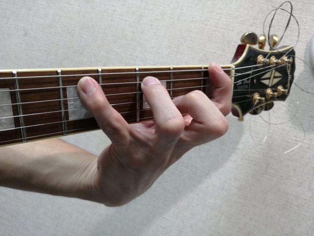 手を広げてギターの指板を押さえている画像