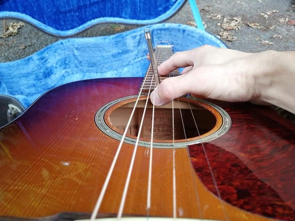 アコースティックギターのトラスロッドネジに六角レンチを差し込んでいるところ