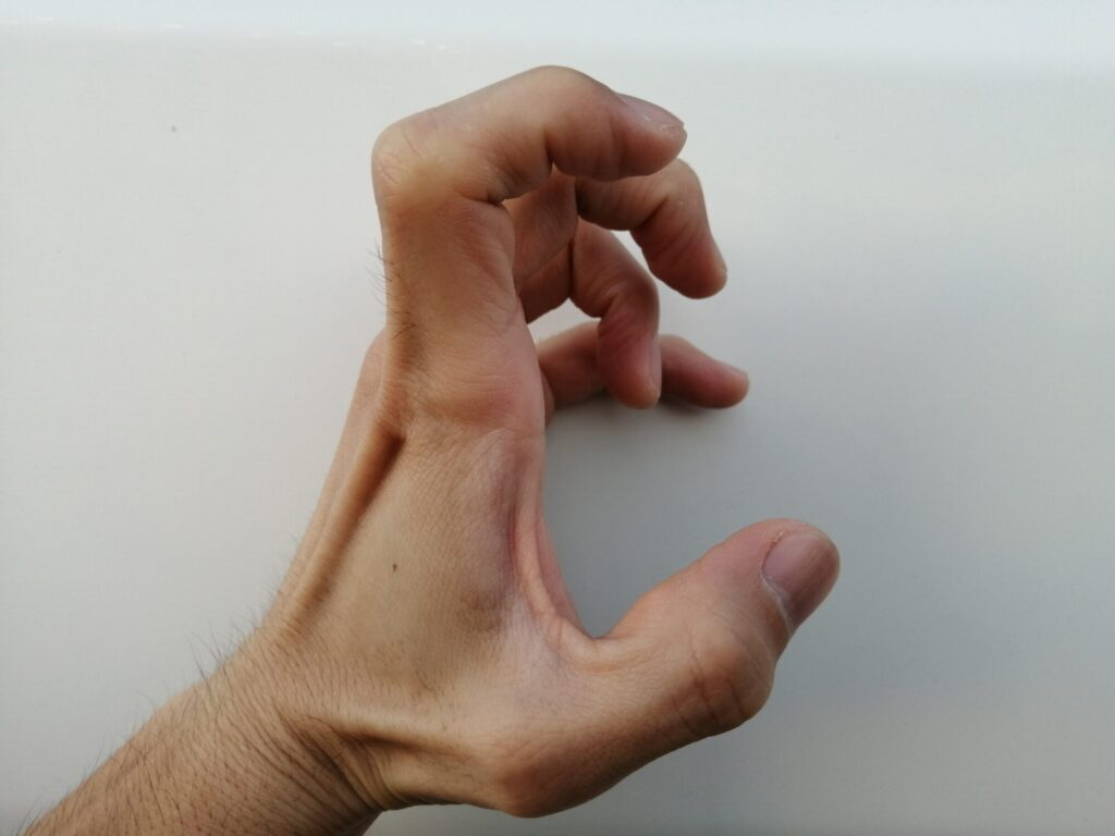 指の関節を曲げた手を横から見ている画像