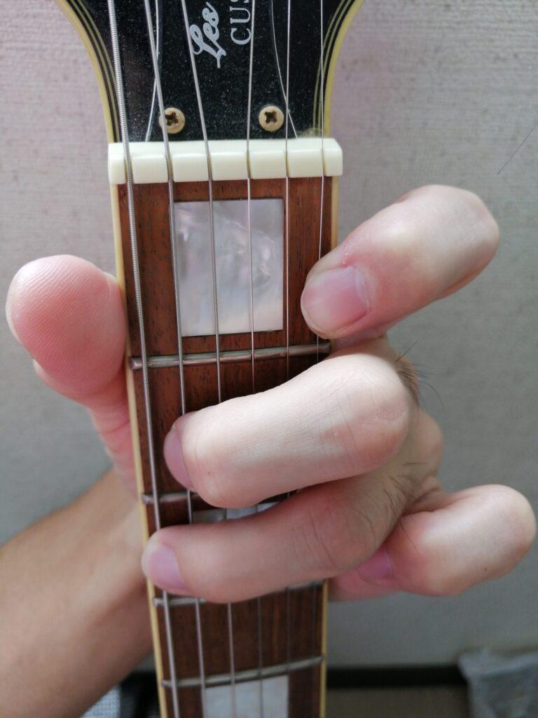 ギターのG7コードを押さえている手