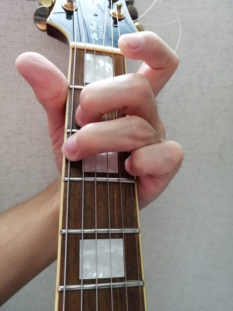 小指でギターの1弦3フレットを押さえているGコード