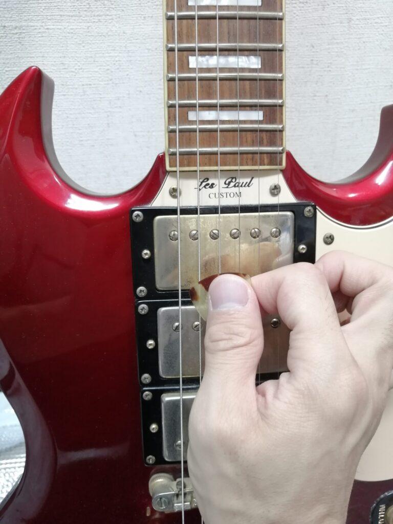 ピックでギターを5弦から弾くイメージ
