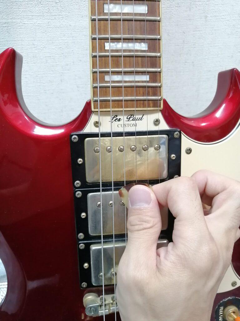 ピックでギターを4弦から弾くイメージ