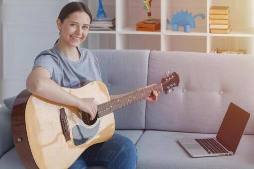 パソコンの前でギターを構える女性