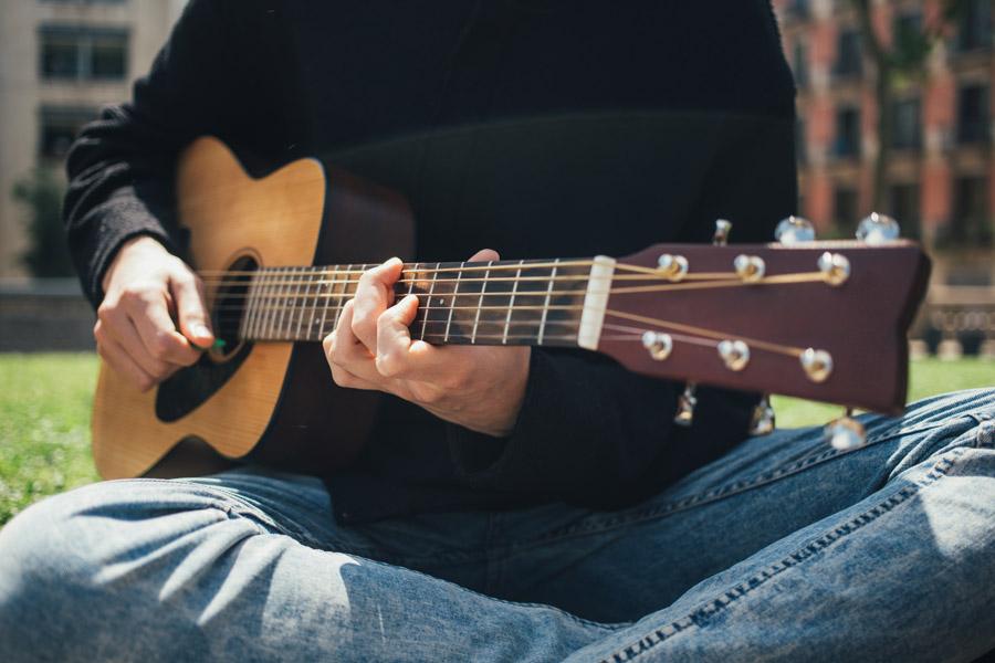 アコースティックギターを弾く男性の画像